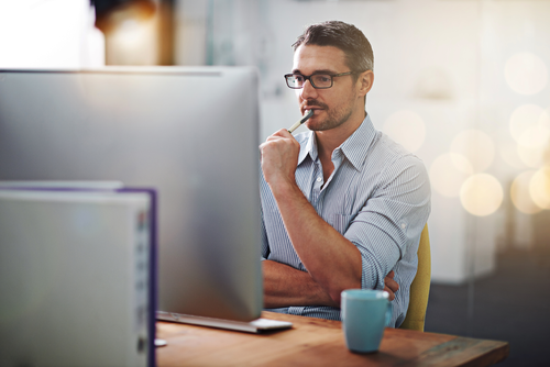 Man with glasses thinking deeply while sat at computer