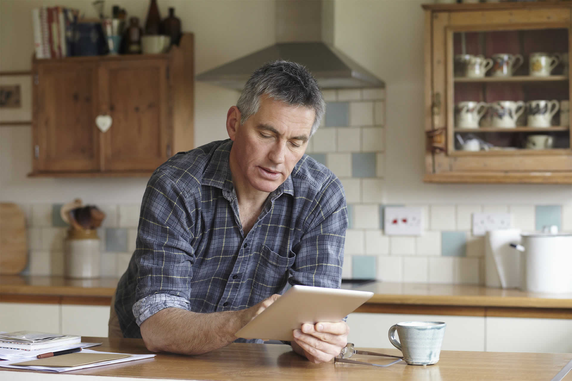 Illustrative picture of a man reviewing his pension from a tablet at home