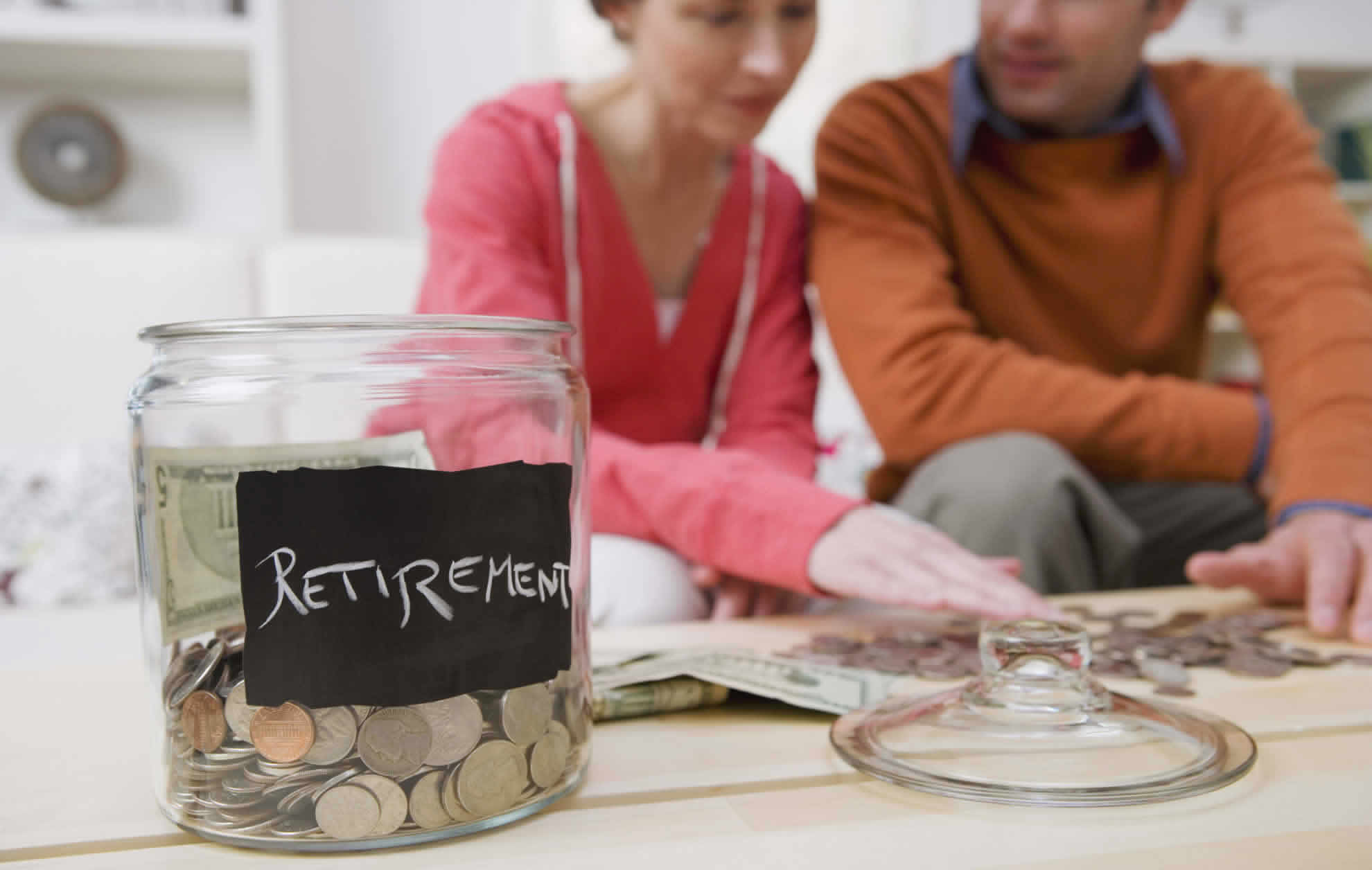 Two people sitting beside a jar of coins representing retirement funds