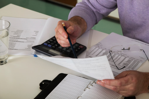man sitting with papers and calculator