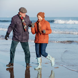 Happy couple walking along a cold beach